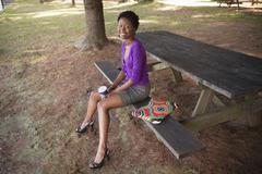African american businesswoman with laptop sitting on picnic bench Stock Photos