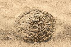 aztec calendar stone carving on sand - stock photo