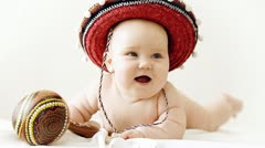 Baby in sombrero hat with maracas on the light background Stock Footage