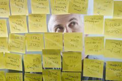 Caucasian businessman looking at adhesive notes on wall Stock Photos