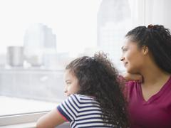 mother and daughter looking out window - stock photo