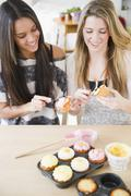 Teenage girls icing cupcakes together Stock Photos