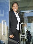 african american businesswoman opening office door - stock photo