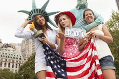 Laughing friends visiting the statue of liberty Stock Photos