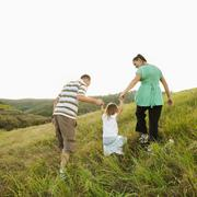 Family holding hands and walking up field Stock Photos