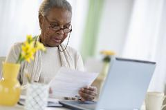Black woman paying bills online Stock Photos