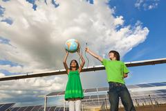 Lapset holding globe lähellä aurinkopaneelit Kuvituskuvat