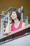 Korean woman talking on cell phone in health club Stock Photos