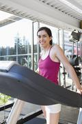 Smiling woman on treadmill in health club Stock Photos