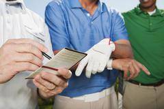Golfer standing with friends writing in golf score card Stock Photos