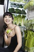 Mixed race woman with apple near green vegetables in refrigerator Stock Photos