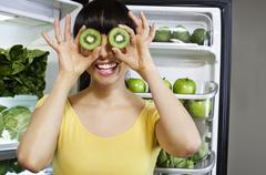 Mixed race woman covering eyes with kiwi slices near refrigerator Stock Photos