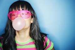 Mixed race woman blowing bubble with bubble gum Stock Photos