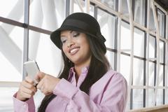 Hispanic teenage girl text messaging on cell phone Stock Photos
