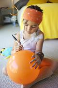 Mixed race girl drawing on balloon Stock Photos