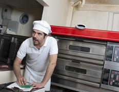Hispanic baker working in commercial kitchen Stock Photos