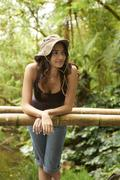 Hispanic woman leaning on railing in forest Stock Photos