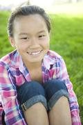 Smiling chinese girl sitting in grass Stock Photos