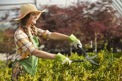 caucasian woman trimming bush in plant nursery - stock photo