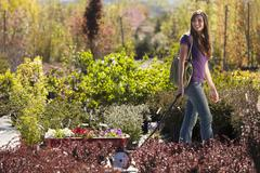 Caucasian woman pulling wagon in plant nursery Stock Photos