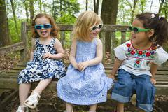 Girls in sunglasses sitting on bench together Stock Photos
