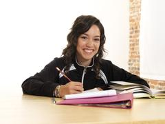 Grinning hispanic teenager doing homework Stock Photos