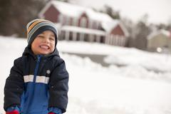 Grinning mixed race boy standing in snow Stock Photos