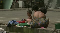 Women Washing Clothes in Manila Street Stock Footage