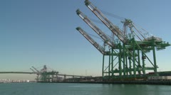 A harbor boat passes beside Long Beach harbor and shipping containers. Stock Footage