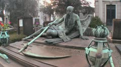 The grim reaper sits on a tomb in a graveyard with his scythe. - stock footage