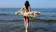 Stock Video Footage of beautiful girl playing in the sea wide shot