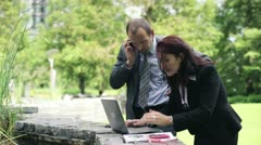 Business people with laptop and cellphone in the park HD - stock footage