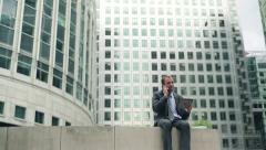 Young businessman with tablet and cellphone in the city HD Stock Footage