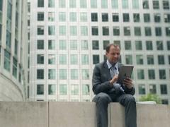 Businessman smoking cigarette and using tablet computer in the city NTSC Stock Footage