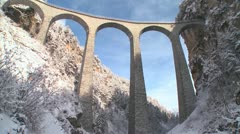 Stock Video Footage of A train in Europe crosses a remarkable bridge and plunges directly into a