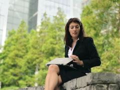 Businesswoman with laptop having a break and relaxing in city park NTSC Stock Footage