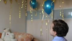 Child throwing balls in a decorated room Stock Footage