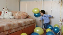 Little boy enthusiasm kicks colorful balloons at home - stock footage