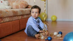 Child trying to unravel the ribbons on the balloons Stock Footage