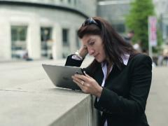 Young businesswoman reading bad news on tablet computer in the city NTSC Stock Footage