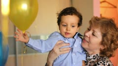 Grandmother of the child keeps him in her arms Stock Footage