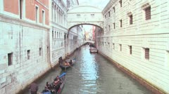 Gondolas pass under the Bridge of Sighs in Venice, Italy. Stock Footage