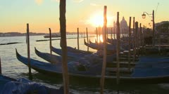 A beautiful shot of the sun setting behind rows of gondolas in Venice, Italy. Stock Footage