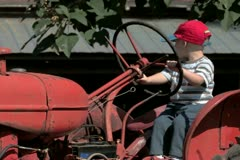 Boy playing on old red tractor Stock Footage