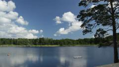 Pan and tilt from sky to swedish lake with raft - stock footage