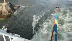 Stern of passenger ferry with Swedish flag passes very close to rocks - stock footage
