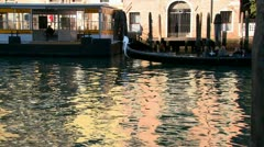A gondola is rowed across beautiful colorful water in Venice, Italy. Stock Footage