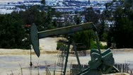 Oil Well Pump With City And Traffic In Background Stock Footage