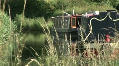 Narrow boat mooring on a canal in England Stock Footage