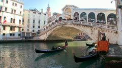 Gondolas under the Rialto Bridge in Venice, Italy. Stock Footage